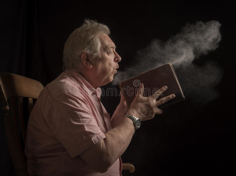 Mature man blowing dust off an old book royalty free stock photo