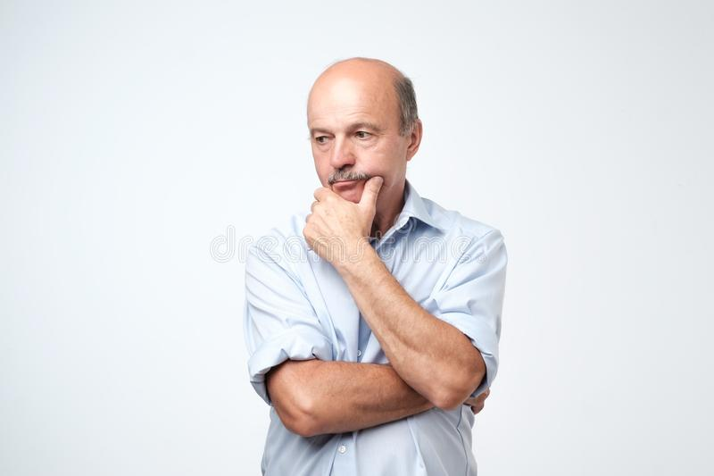 Mature man in blue shirt thinking and looking puzzled. royalty free stock photography