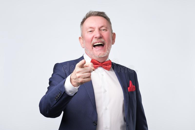 Mature man in blue suit pointing finger and toothy smile. Studio shot. Mock or bad joke concept. Mature man in blue suit pointing finger and toothy smile. Studio royalty free stock photo