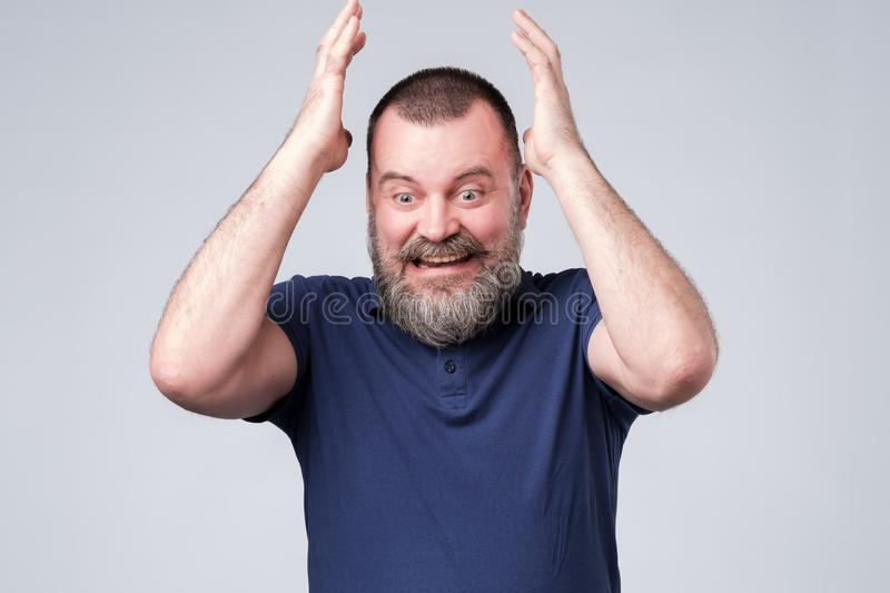 Mature man in blue t-shirt expressive gesticulating with hands, trying to prove his opinion. stock image