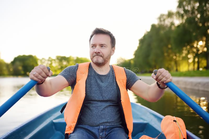 Mature man boating on a river or pond at sunny summer day. Rest and traveling royalty free stock images