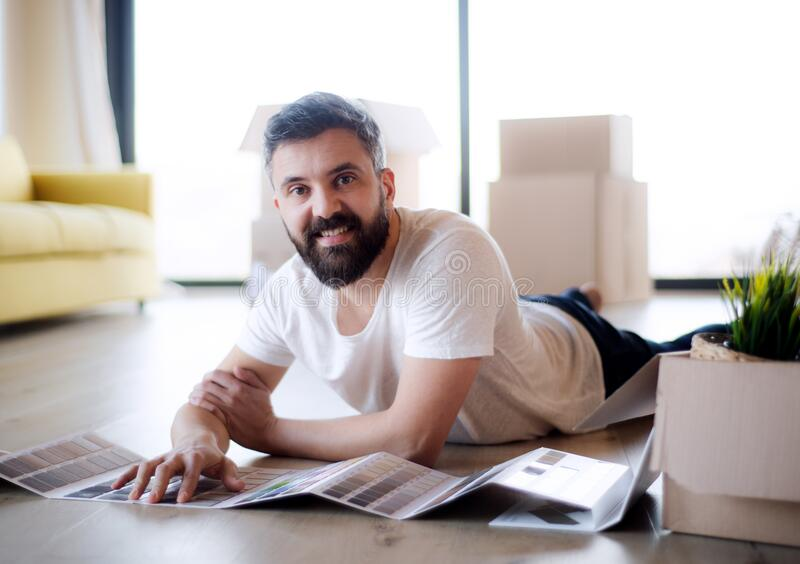 Mature man with boxes moving in new house, looking at color swatch. royalty free stock image