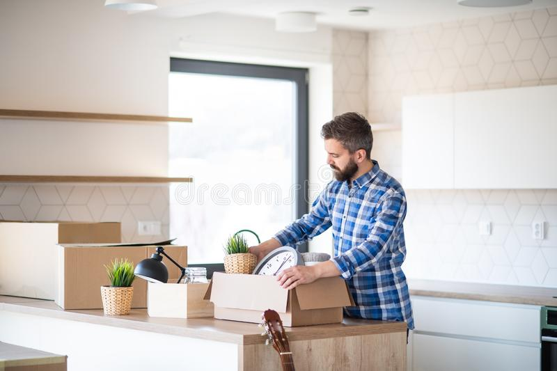 Mature man with boxes moving in new unfurnished house, unpacking. stock images