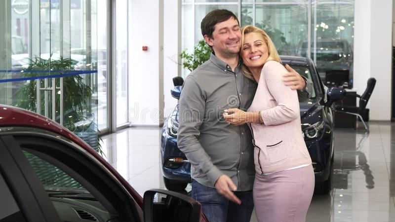Mature man buying a new car for his gorgeous wife at the dealership salon royalty free stock images