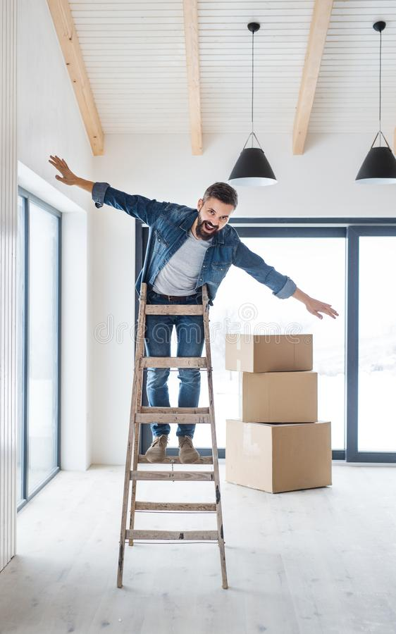 A mature man with cardboard boxes standing on a ladder, furnishing new house. stock photos