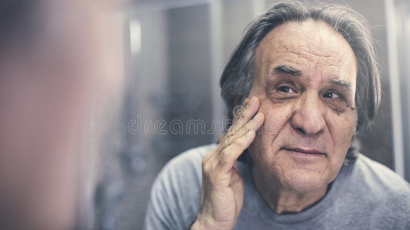 Mature man checking his wrinkles. Mature man checking his  wrinkles stock photo