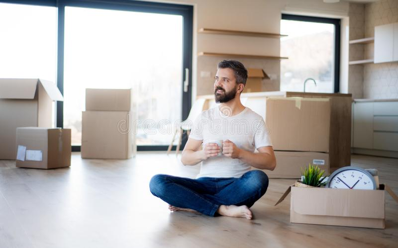 Mature man with coffee and boxes moving in new house, unpacking. royalty free stock image