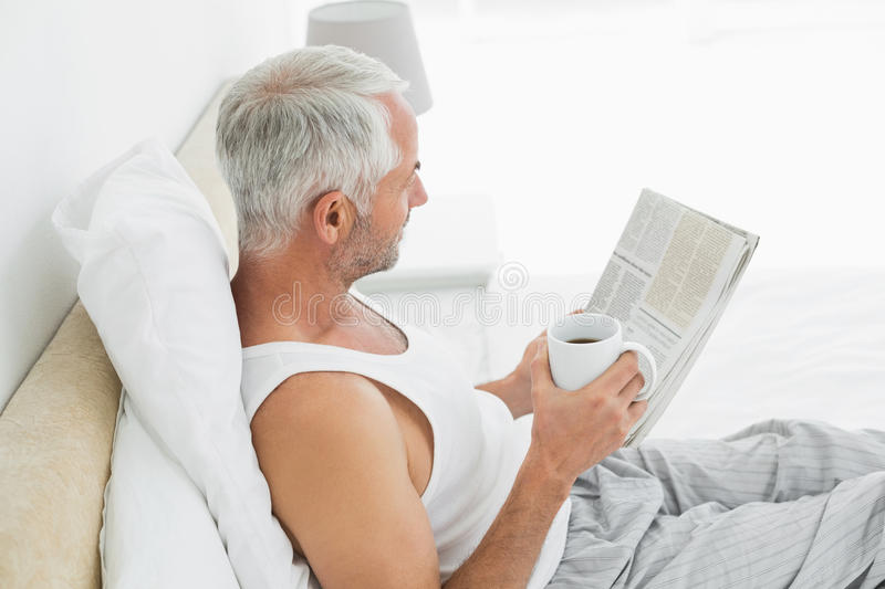 Mature man with coffee cup and newspaper in bed royalty free stock photo