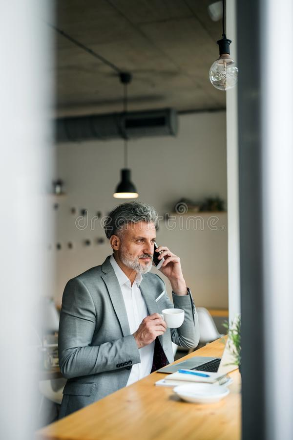 Mature man with coffee and smartphone at the table in a cafe. royalty free stock photo