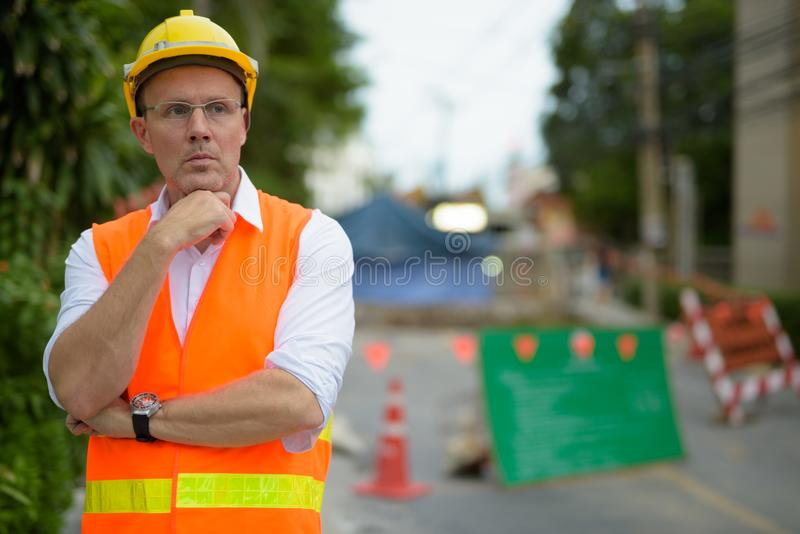 Mature man construction worker at the construction site in the c royalty free stock image