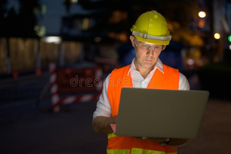 Mature man construction worker at the construction site in the c. Portrait of mature man construction worker at the construction site in the city at night royalty free stock image