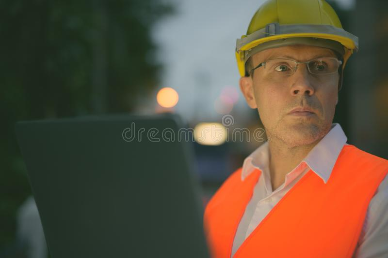 Mature man construction worker at the construction site in the city at night. Portrait of mature man construction worker at the construction site in the city at royalty free stock image