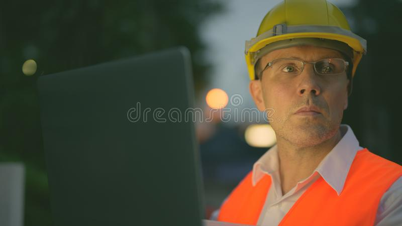 Mature man construction worker at the construction site in the city at night. Portrait of mature man construction worker at the construction site in the city at stock images