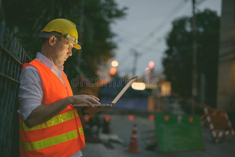 Mature man construction worker at the construction site in the city at night. Portrait of mature man construction worker at the construction site in the city at stock photos