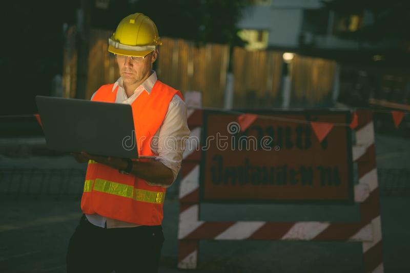 Mature man construction worker at the construction site in the city at night. Portrait of mature man construction worker at the construction site in the city at stock image