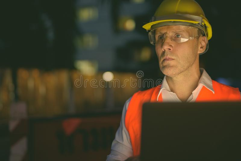 Mature man construction worker at the construction site in the city at night stock image