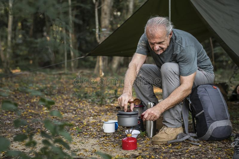 Mature man cooking at a campsite royalty free stock images