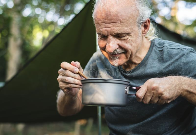 Mature man cooking at a campsite royalty free stock photo