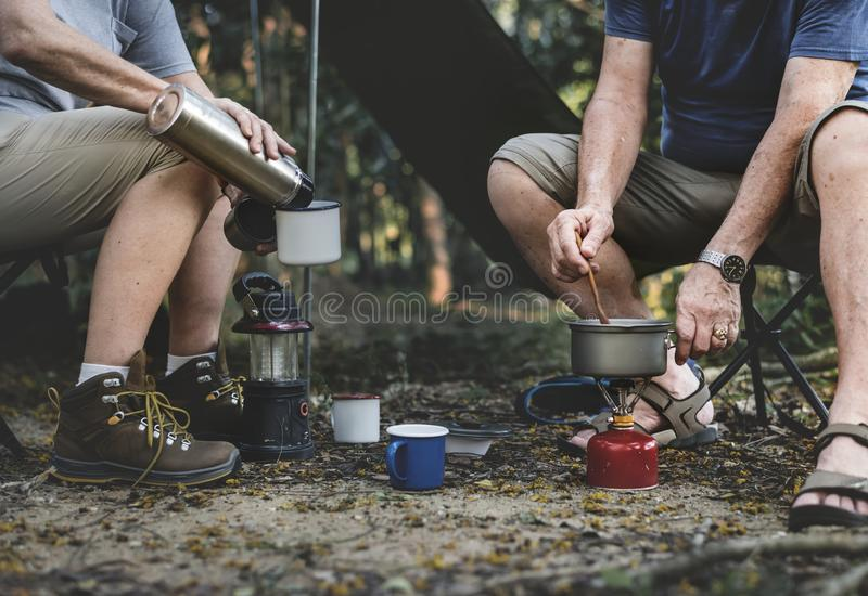 Mature man cooking at a campsite stock images