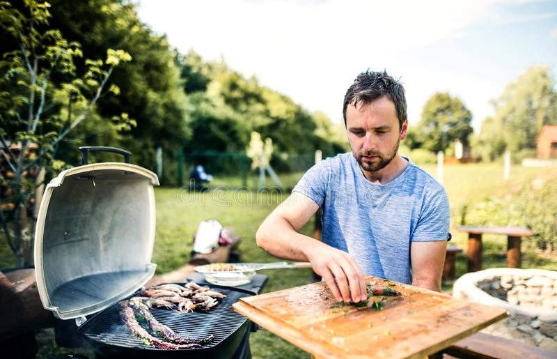 Mature man cooking seafood on a barbecue grill in the backyard. Mature man cooking seafood on a barbecue grill in the backyard on a sunny day royalty free stock photos