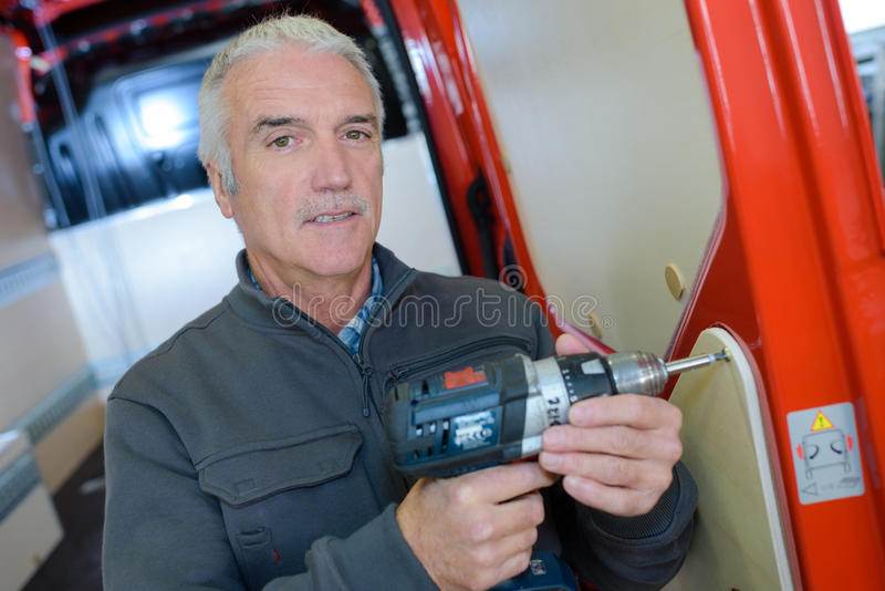 Mature man with drill at construction site royalty free stock images