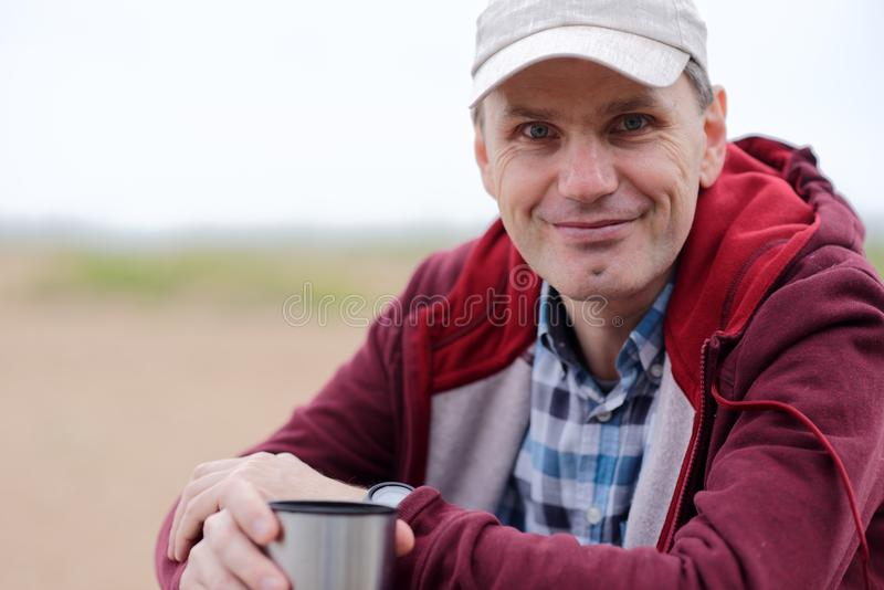 Man drinking tea on a beach stock photography