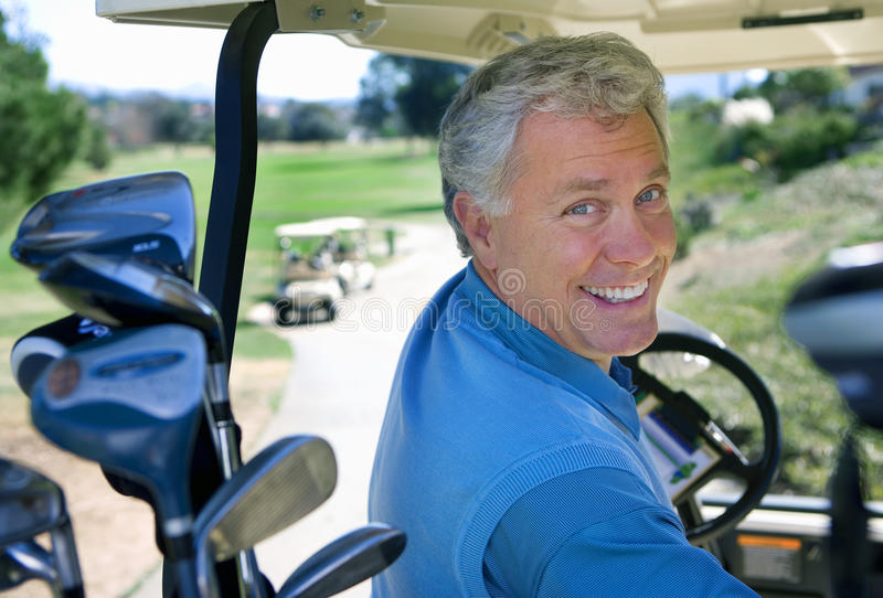 Mature man driving golf buggy on golf course, looking over shoulder, smiling, close-up, rear view, portrait royalty free stock photos