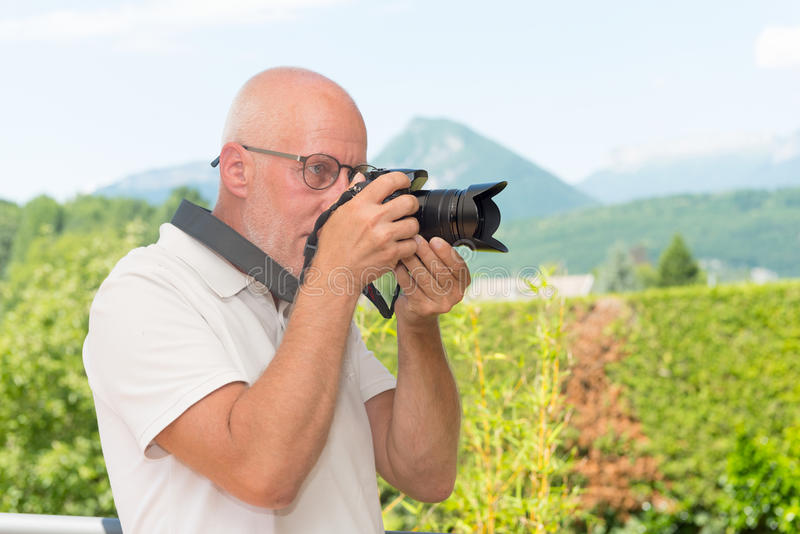 Mature man with dslr camera, outdoors royalty free stock photos