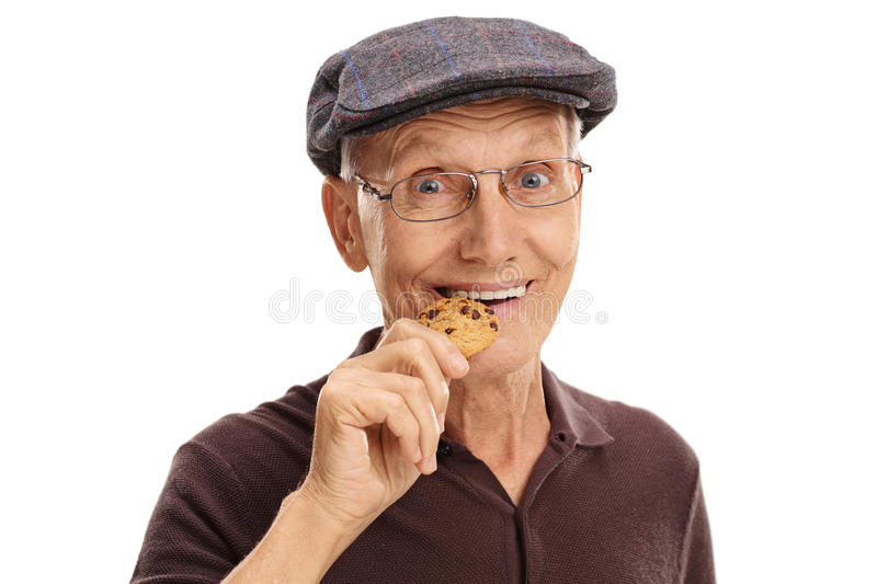 Mature man eating a chocolate chip cookie. Close-up on a mature man eating a chocolate chip cookie isolated on white background stock image