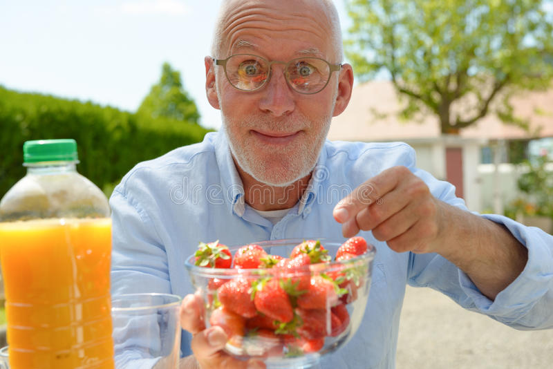 Mature man eating strawberry, outside royalty free stock photo