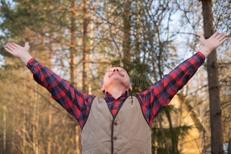 Mature man enjoying life outdoor raising hands up. royalty free stock image