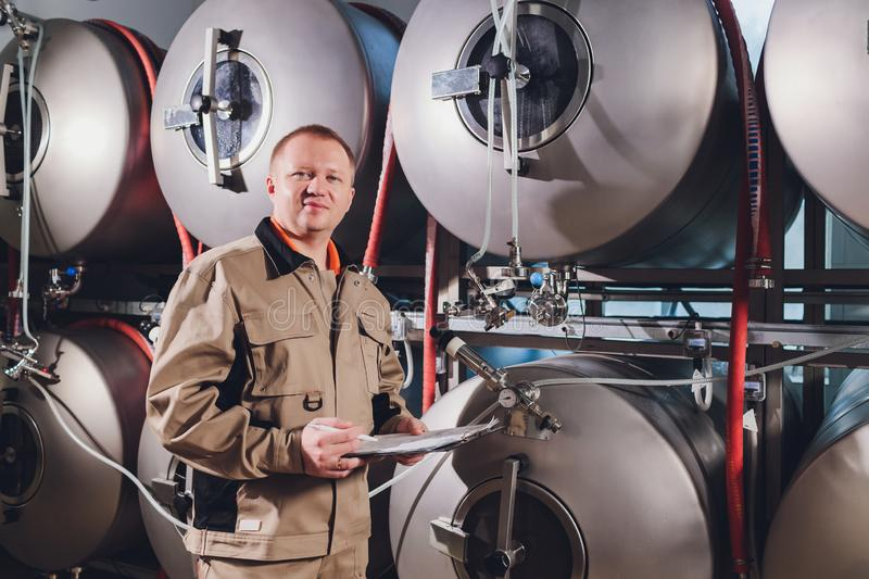 Mature man examining the quality of craft beer at brewery. Inspector working at alcohol manufacturing factory checking stock photography