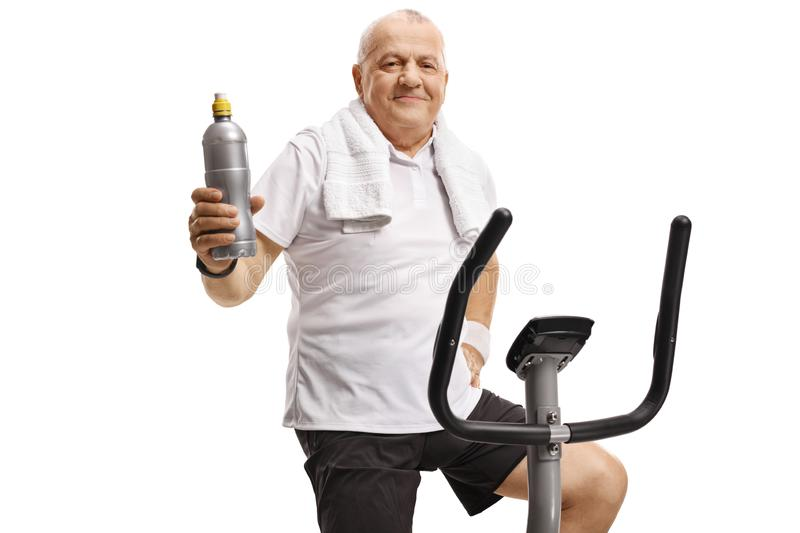 Mature man on an exercise bike holding a water bottle stock photo