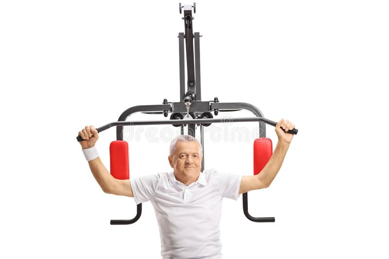 Mature man exercising on a fitness machine royalty free stock photography
