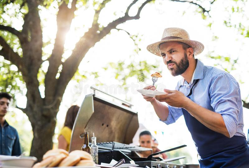 A mature man with family and friends cooking and serving food on a barbecue party. stock image