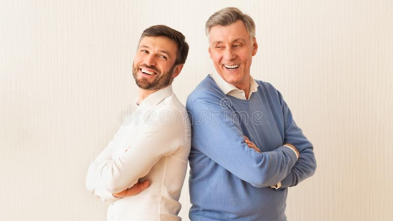 Mature Man And Father Standing Back-To-Back Crossing Hands, White Background royalty free stock photo