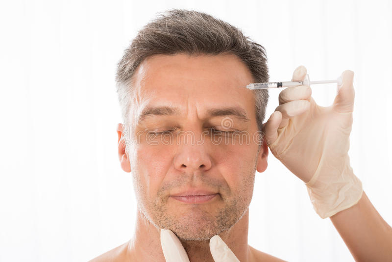 Mature Man Get Injection On His Face. Close-up Of Mature Man Get Injection On His Face royalty free stock photo