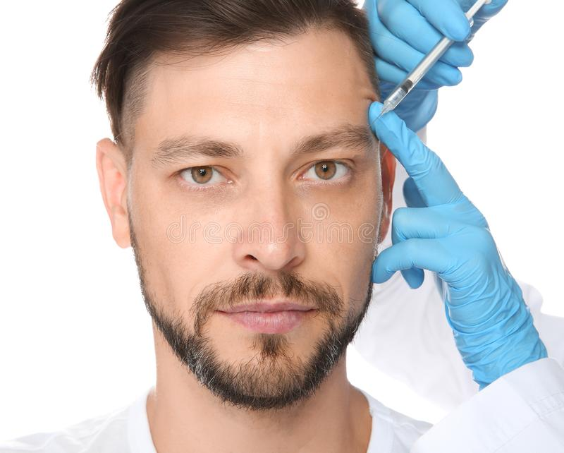Mature man getting facial injection on white background. Cosmetic surgery concept stock photo