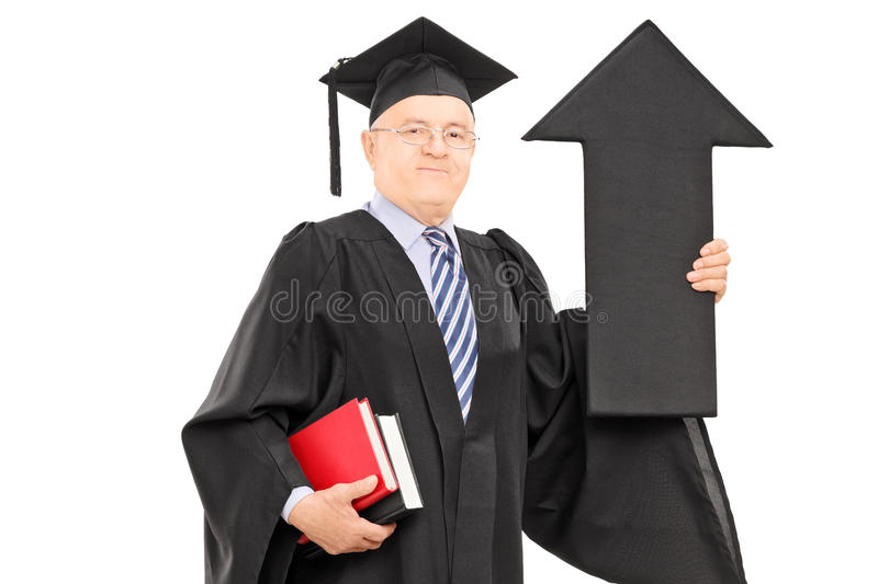 Mature man in graduation gown holding arrow pointing up. Mature man in graduation gown holding big black arrow pointing up isolated on white background royalty free stock photos