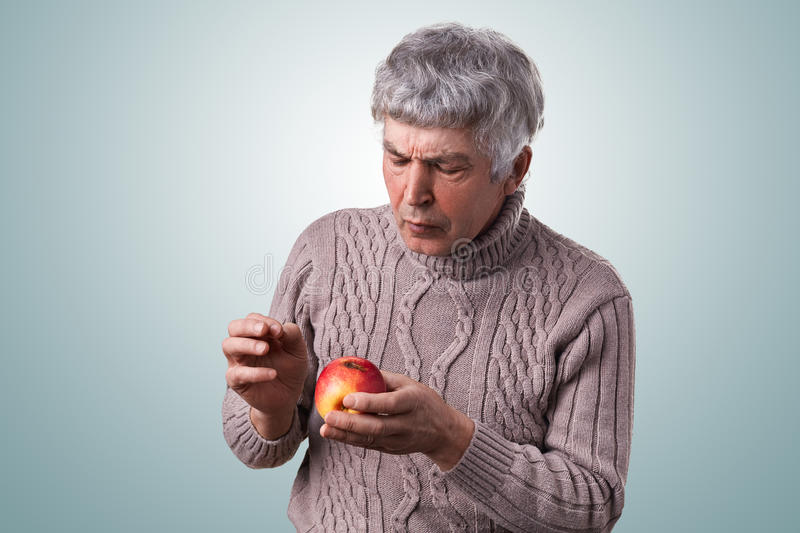 A mature man with gray hair dressed in sweater holding a spoiled apple looking at it attentively examining it. Senior man holding royalty free stock image