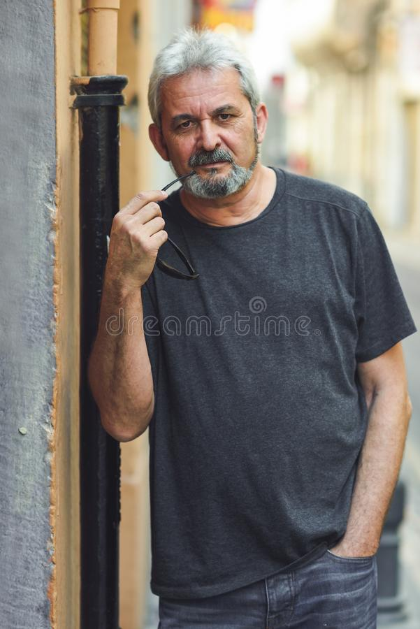 Mature man with grey hair standing in urban background stock photo