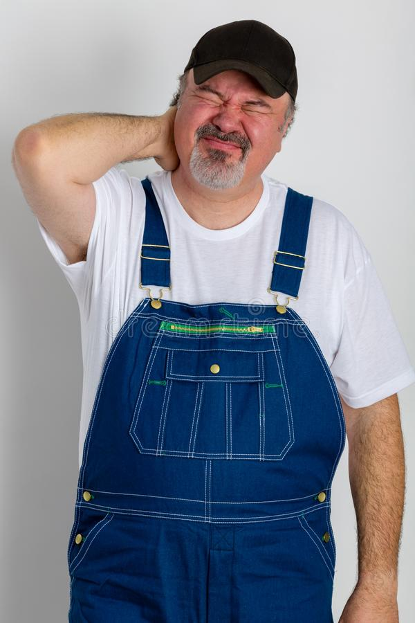 Man wearing dungarees holding his painful neck royalty free stock photography