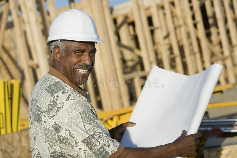 Mature Man In Hardhat With Blueprint At House Construction Site stock photography