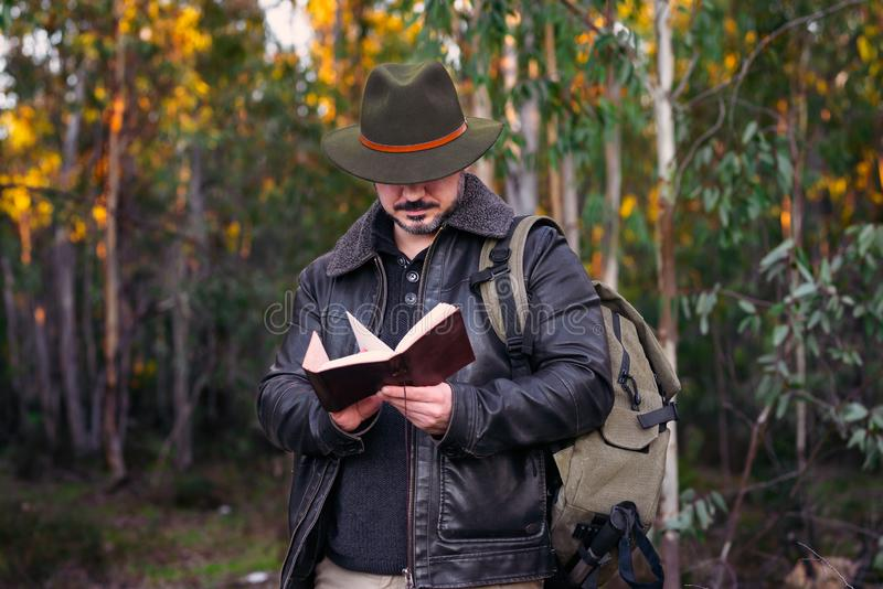 Mature man with hat and jacket looking old book on forest with copy space for text stock photography