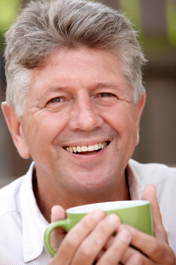 Mature man having a drink stock photo