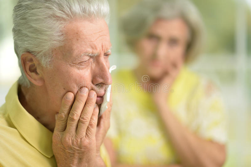 Mature man having toothache, his wife stock photography