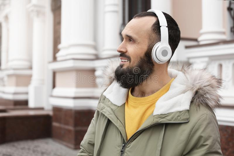 Mature man with headphones listening to music outdoors. Space for text royalty free stock images