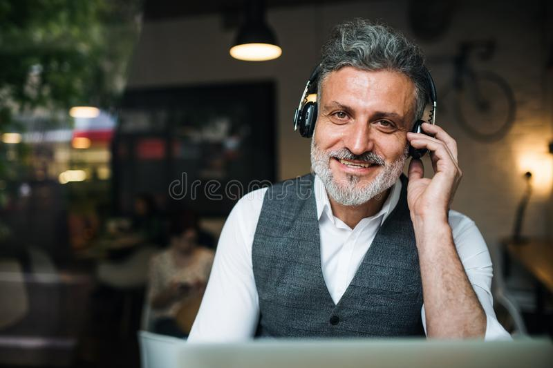 Mature man with headphones at the table in a cafe, using laptop. Shot through glass royalty free stock photos