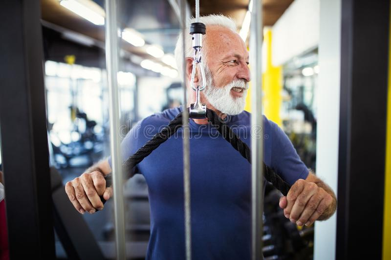 Mature man in health club doing exercise to stay healthy royalty free stock photography
