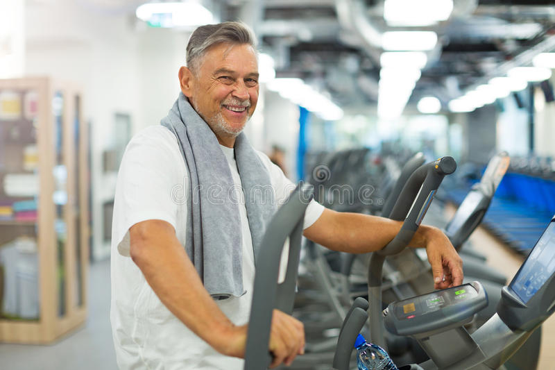 Mature man in health club. Mature man doing fitness exercises royalty free stock image
